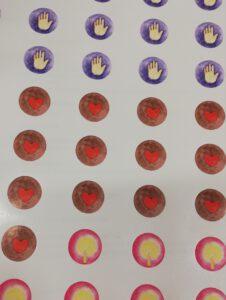 Kuvassa ympyränmuotoisia tarroja, joissa käden, liekin ja sydämen kuvia.