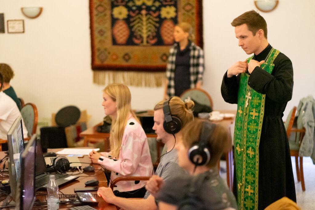 Kuvassa näkyy nuoria istumassa livelähteyksen teossa, osalla on kuulokkeet korvillaan. Heidän takanaan seisoo pappi pukien päälleen vihreää epitrakiilia.